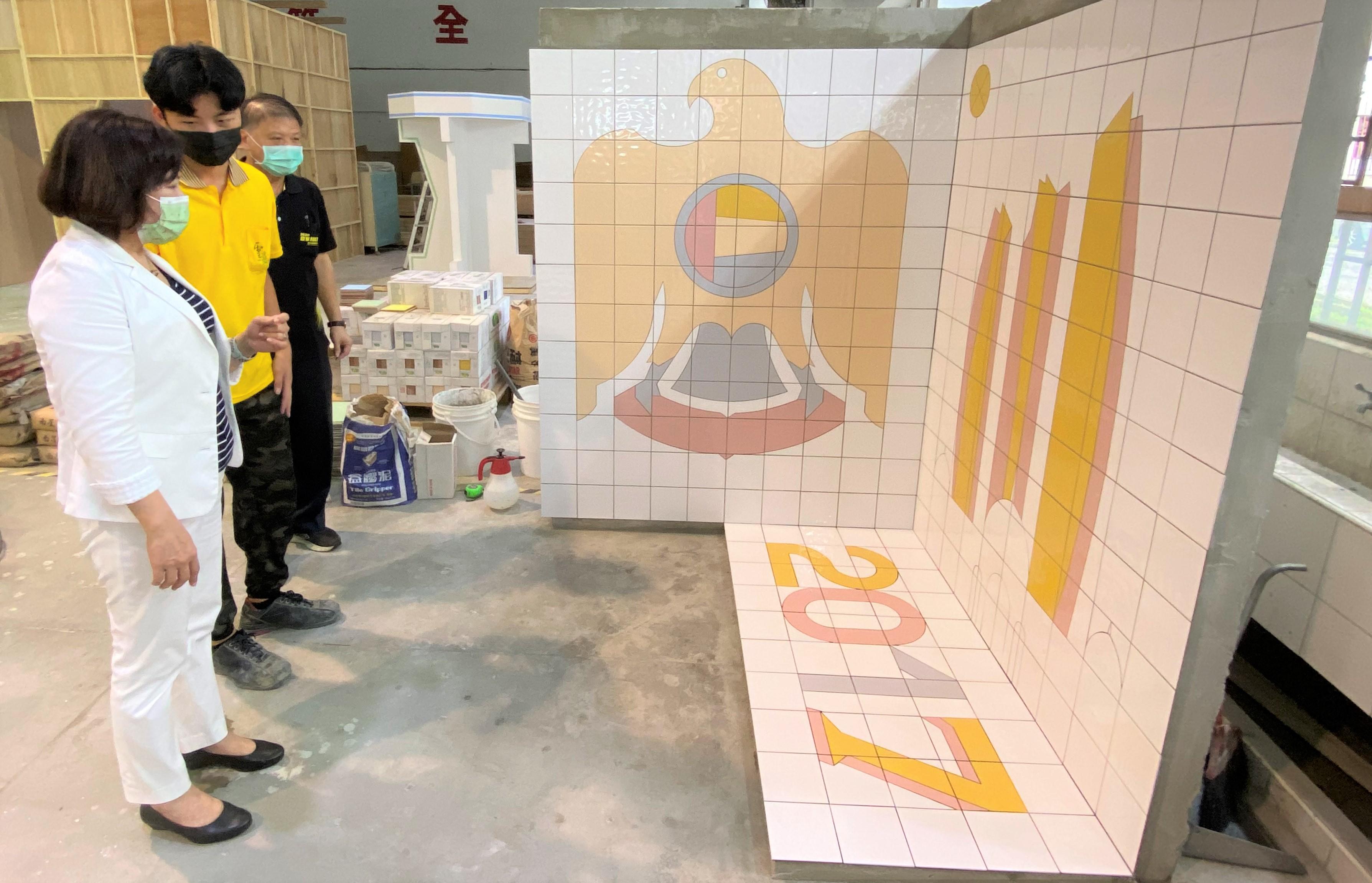 ▲舖面國手陳泰源(左)向阿春部長解說作品