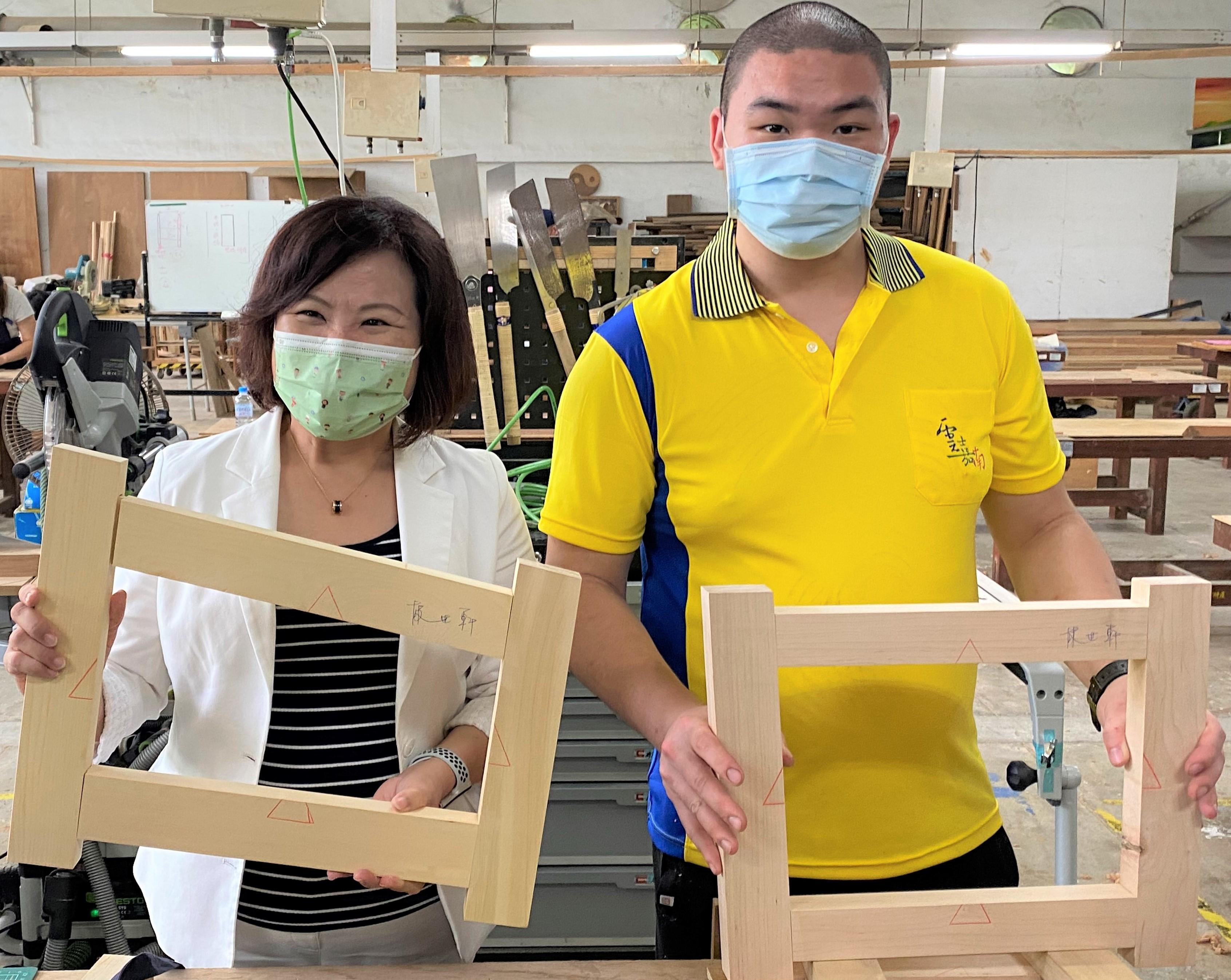 ▲木工國手林世軒(左)向阿春部長(右)展示作品